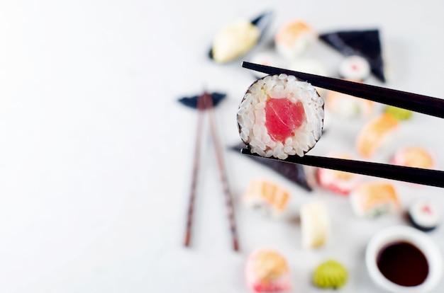 Smaczne roladki sushi zestaw z sosami, pałeczkami, imbirem na stole. dostawa japońskiego jedzenia
