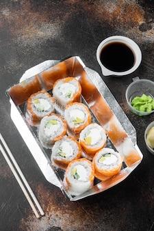 Smaczne rolki sushi w zestawie jednorazowych pudełek, na starym ciemnym rustykalnym