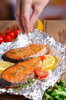 Smaczne ryby pieczone w folii na stole z bliska