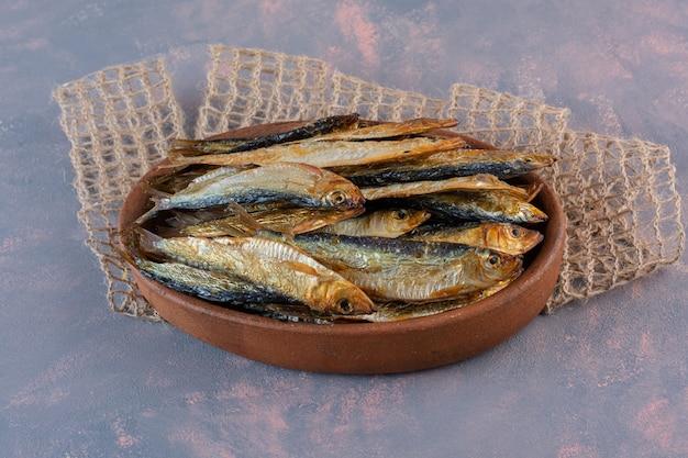 Smaczne ryby solone na drewnianym talerzu, na tle marmuru.