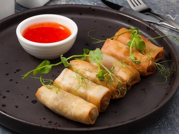 Smaczne sajgonki z ostrym sosem i mikro zieleniną na ciemnym talerzu