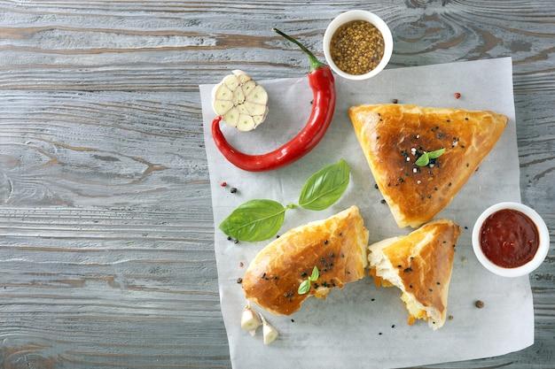 Smaczne samosy z sosami na drewnianym stole