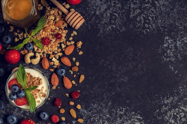 Smaczne składniki (muesli, miód, jagody, jogurt i orzechy) na śniadanie.