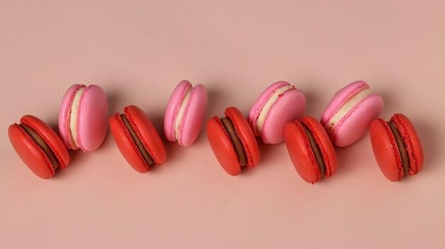 Smaczne słodkie ciasteczka, czerwone i różowe makaroniki na różowym tle, widok z góry, orientacja pozioma, zbliżenie