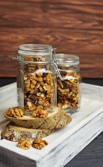 Smaczne słodkie i zdrowe przekąski orzechy włoskie w szklanym słoiku w drewnianej skrzyni białej tablicy