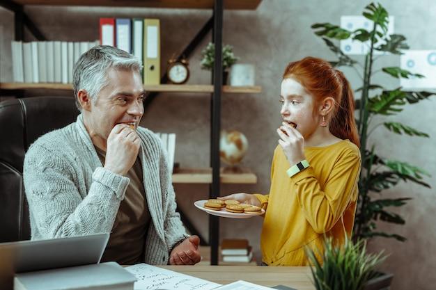 Smaczne słodycze. radosny miły ojciec i córka patrzą na siebie podczas jedzenia ciastek