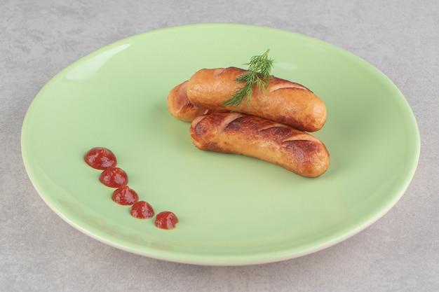 Smaczne smażone kiełbaski i keczup na zielonym talerzu.
