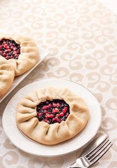 Smaczne śniadanie. domowa słodka galette z czarnymi jagodami i borówkami na talerzu