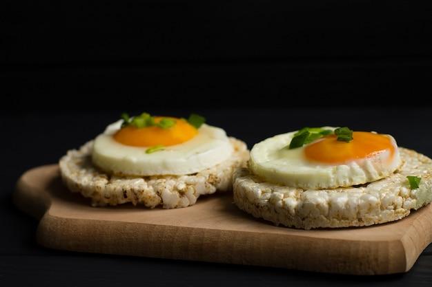 Smaczne śniadanie. jajka sadzone, gotowane, z pieczywem chrupkim. chleb ryżowy, koncepcja zdrowego odżywiania.