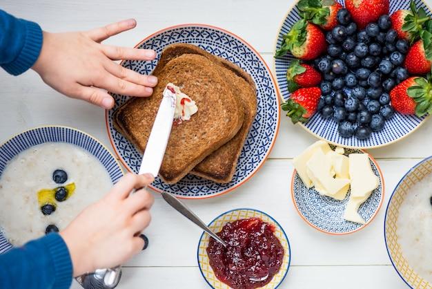 Smaczne śniadanie rodzinne z grzankami, owsianką, jagodami