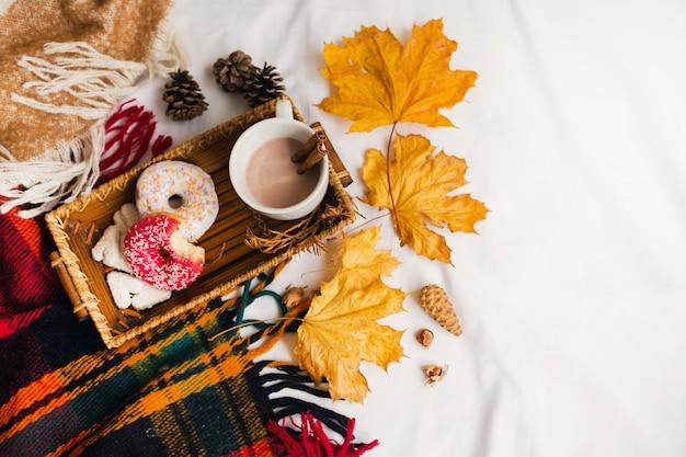 Smaczne śniadanie w łóżku na drewnianej tacy z filiżanką kakao, cynamonem, ciasteczkami i glazurowanymi pączkami.
