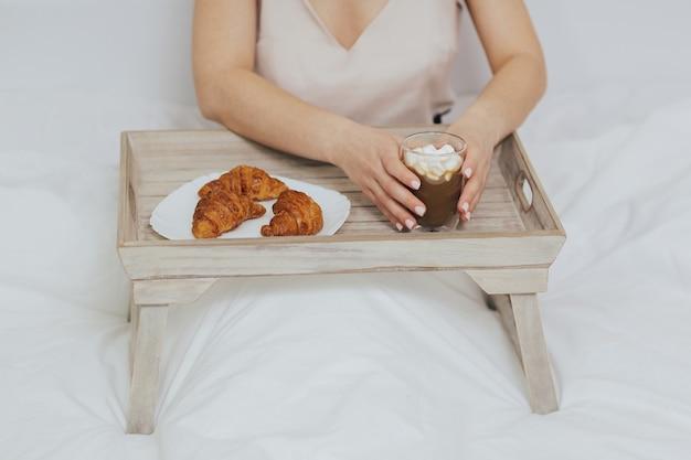 Smaczne śniadanie w łóżku z cappuccino i rogalikami