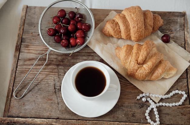 Smaczne śniadanie ze świeżym croissantem, kawą, wiśniami na drewnianej tacy. espresso na tacy śniadaniowej. śniadaniowy naszyjnik z pereł