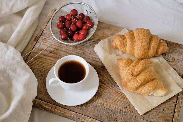 Smaczne śniadanie ze świeżym croissantem, kawą, wiśniami na drewnianej tacy. espresso na tacy śniadaniowej