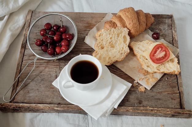Smaczne śniadanie ze świeżym croissantem, kawą, wiśniami na drewnianej tacy. obfity rogalik z pomidorem i serem. espresso na tacy śniadaniowej