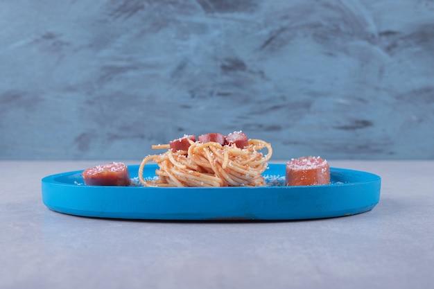 Smaczne spaghetti z kiełbaskami na niebieskim talerzu.
