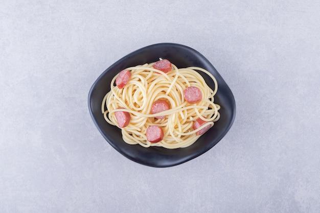 Smaczne spaghetti z pokrojonymi kiełbaskami w czarnej misce.