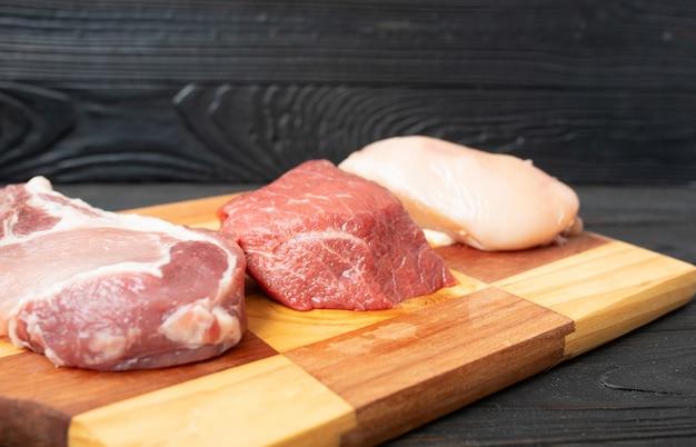 Smaczne surowe mięso cielęce lub wołowe na drewnianej desce do krojenia