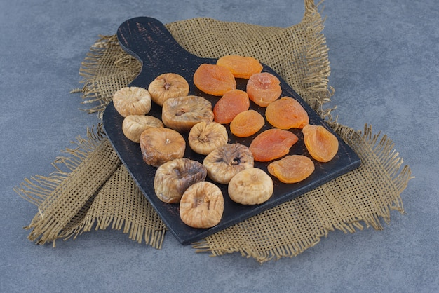 Smaczne suszone owoce na desce, na trójnogu, na marmurowym tle.