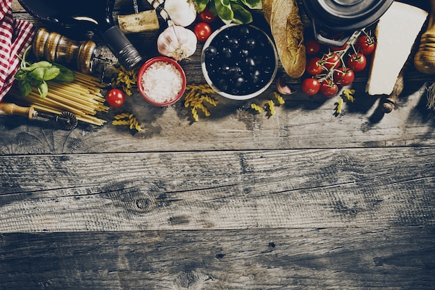 Smaczne świeże apetyczne włoskie składniki żywności na starym rustykalnym drewnianym tle. gotowy do gotowania. strona główna włoskiej kuchni zdrowej żywności koncepcji. tonowanie.