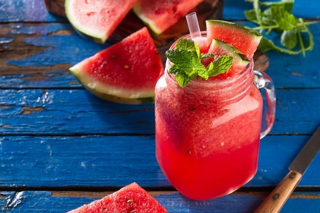 Smaczne świeże apetyczny aromat arbuza napój z miętą na niebieskim stole. przeznaczone do walki radioelektronicznej.