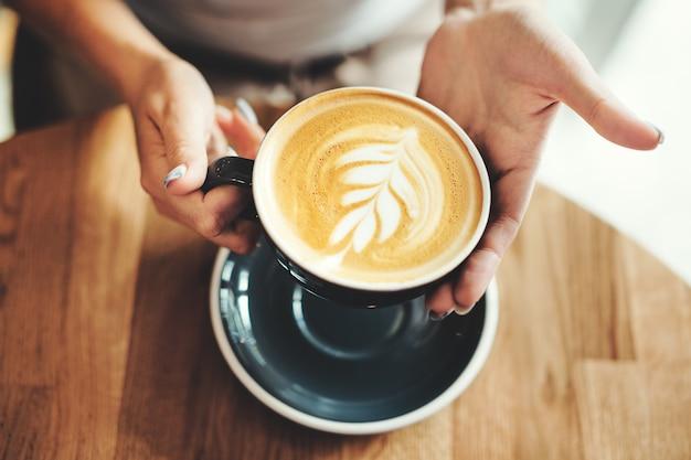 Smaczne świeże cappuccino w filiżance na drewnianym stole. nie do poznania kobieta trzyma kubek w ręce.