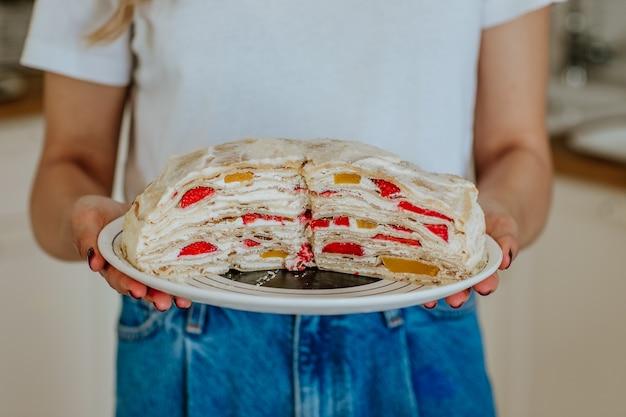 Smaczne świeże ciasto z owocami w ręce kobiety