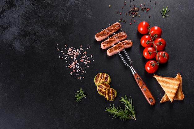 Smaczne, świeże kiełbaski grillowane z przyprawami warzywnymi i ziołami. zdjęcie gotowego dania na ciemnym betonowym stole