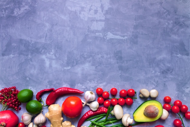 Smaczne świeże letnie surowe organiczne przeciwutleniacze kolorowe warzywa i owoce warzywa: awokado, pomidor, czosnek, chili, imbir na białym tle na szarym tle. wegańskie i wegetariańskie zdrowe jedzenie koncepcja jedzenia