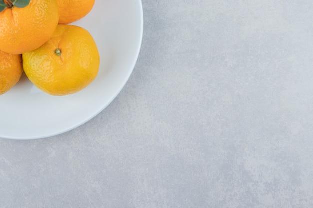 Smaczne świeże mandarynki na białym talerzu.