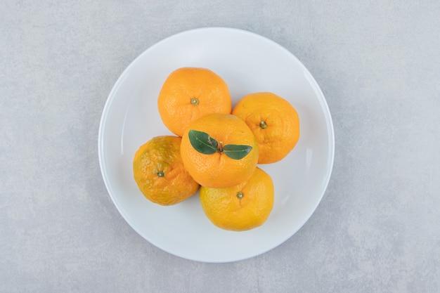 Smaczne świeże mandarynki na białym talerzu