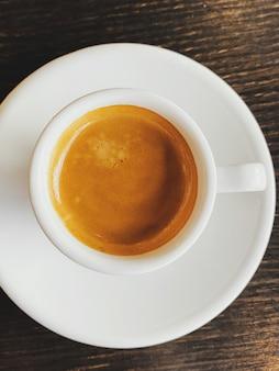 Smaczne, świeże włoskie espresso w biały ceramiczny kubek na stole w kawiarni
