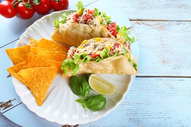 Smaczne taco z frytkami nachos i warzywami na talerzu na stole