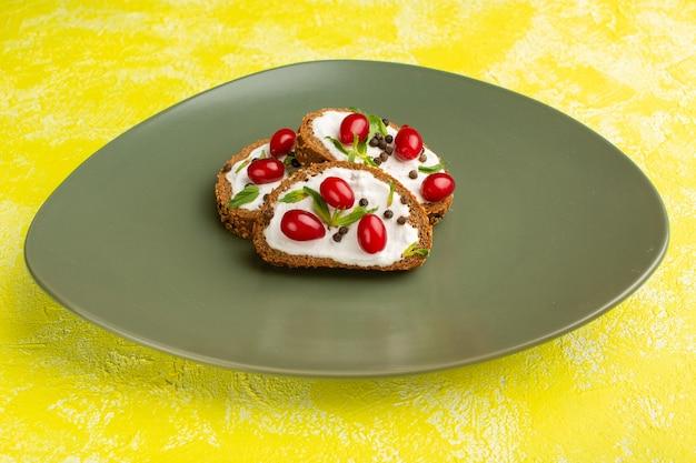 Smaczne tosty z chleba ze śmietaną i dereniami wewnątrz zielonego talerza na żółto