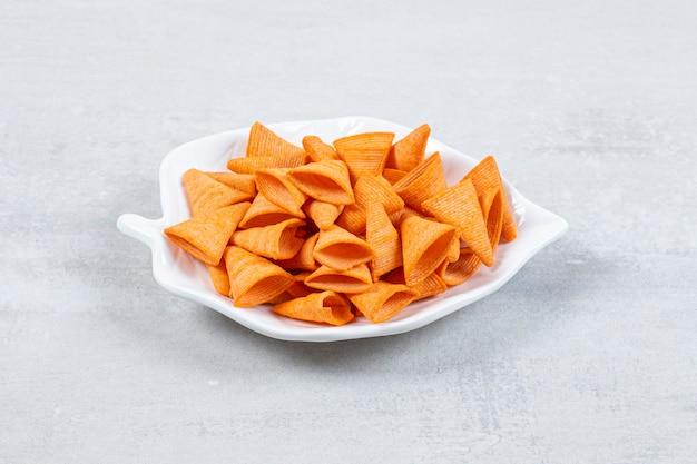 Smaczne trójkątne chipsy na talerzu w kształcie liścia.