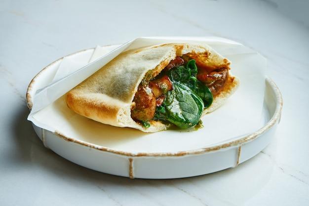 Smaczne uliczne jedzenie - pita z hummusem i pieczarkami, szpinakiem i pomidorami w pergaminie na białym ceramicznym talerzu na marmurowej powierzchni. kuchnia grecka ścieśniać