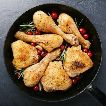 Smaczne upieczone udka z kurczaka z przyprawami na patelni