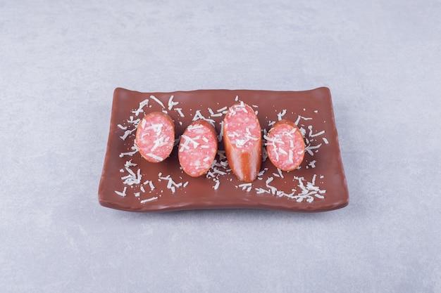 Smaczne wędzone kiełbaski na brązowym talerzu.