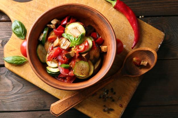 Smaczne wegetariańskie ratatouille z bakłażanów, dyni, pomidorów w misce na drewnianym stole