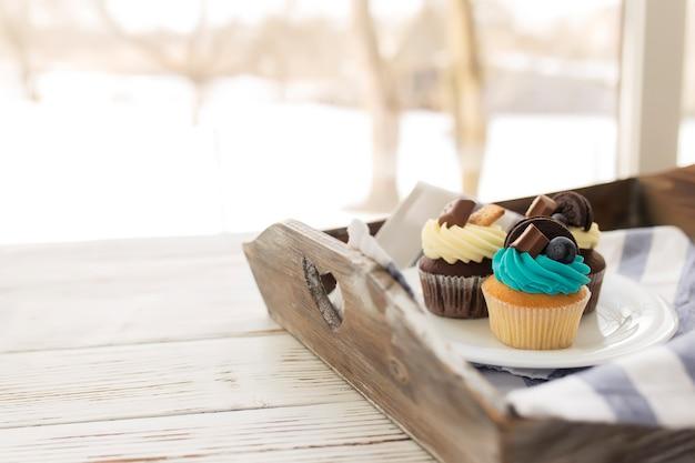 Smaczne wielobarwne babeczki i babeczki na białym talerzu na drewnianej tacy z ręcznikiem. ozdobiony różnymi cukierkami, ciasteczkami i kolorowym słodkim serkiem śmietankowym na wierzchu.