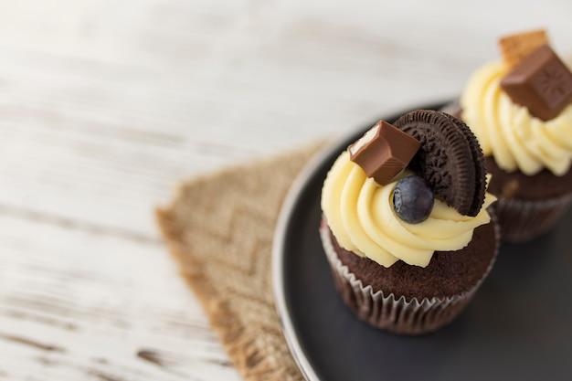 Smaczne wielobarwne babeczki i babeczki na tacy, drewnianym stole. ozdobiony różnymi cukierkami, ciasteczkami, jagodami i kolorowym słodkim serkiem śmietankowym.