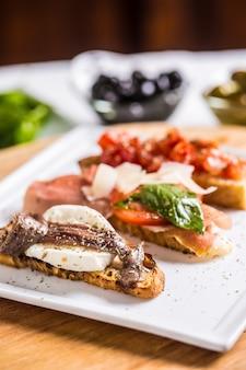 Smaczne włoskie bruschetty z przekąskami z pomidorami, anchois prosciutto i mozarellą.
