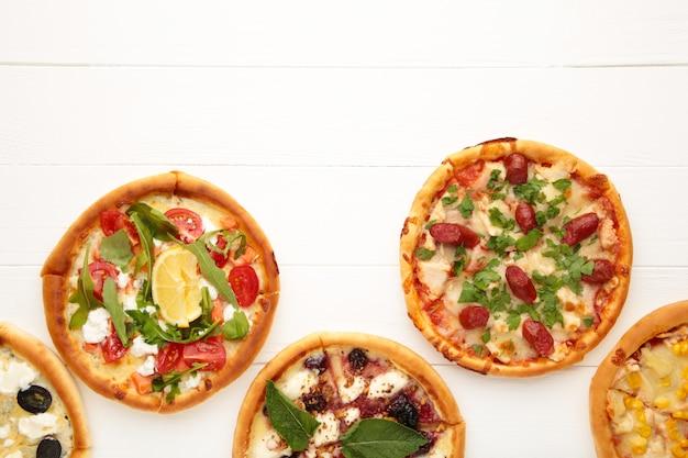 Smaczne włoskie pizze na drewnianym stole