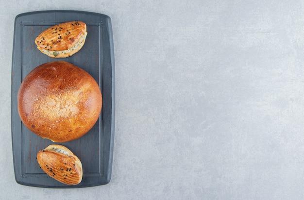 Smaczne wypieki z serem i bułką na czarnej tablicy.