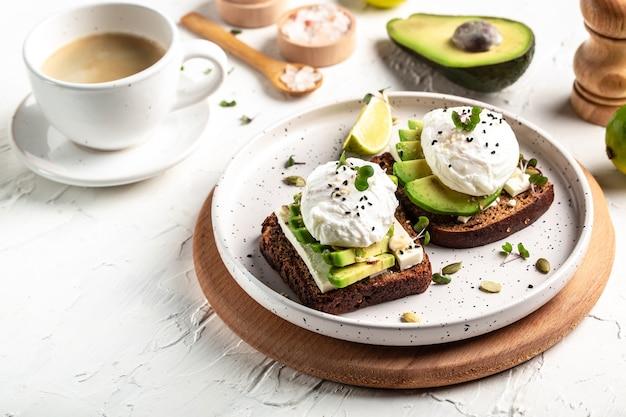 Smaczne zdrowe śniadanie tosty z awokado i jajkiem w koszulce, filiżanka kawy na białym talerzu
