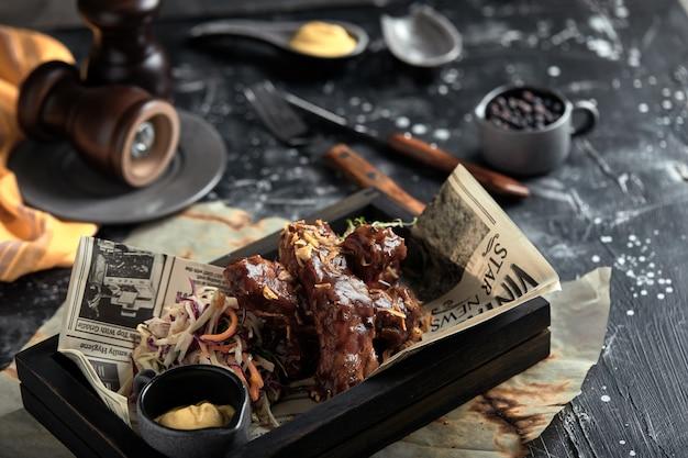 Smaczne żeberka z grilla doprawione pikantnym sosem i posiekanymi świeżymi warzywami na starej rustykalnej drewnianej desce do krojenia z musztardą