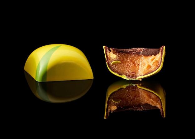 Smaczne żółte cukierki czekoladowe na czarnym tle