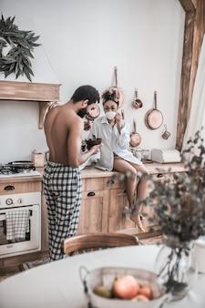 Smacznego. ciemnoskóry mężczyzna bez koszuli stojący z jedzeniem płyty i kobieta w koszuli siedzi z kawą na kuchennym stole