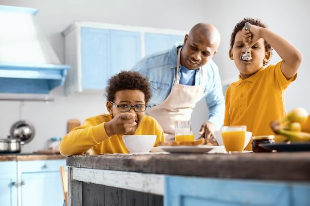 Smacznego. miły, troskliwy ojciec obserwujący swoich synów jedzących śniadanie podczas jedzenia płatków śniadaniowych