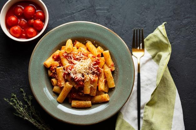 Smaczny apetyczny klasyczny włoski makaron z sosem pomidorowym, parmezanem i makaronem na talerzu na ciemnym stole. widok z góry, poziomy. makaron włoski. makaron penne w sosie pomidorowym z kurczakiem, pomidorami.